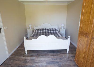 De achterste slaapkamer met tweepersoonsbed van Vakantiehuisje Smoek Holwerd.