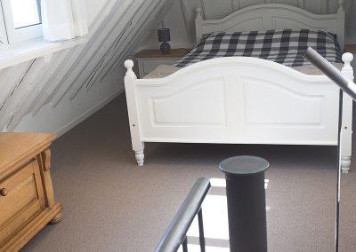 De knusse slaapkamer van Vakantiehuisje Smoek op de verdieping met een tweepersoonsbed